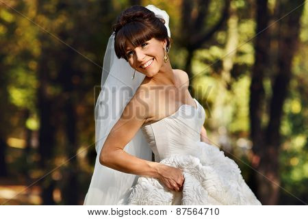 Bride Holding A Dress And Smiling