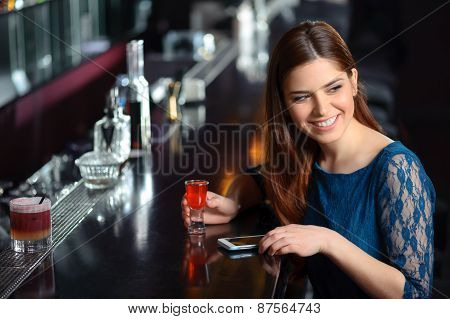 Young woman uses her phone in the bar