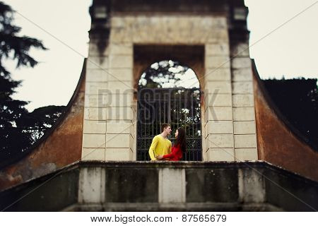 Beautiful Couple Walking Under Ancient Arch
