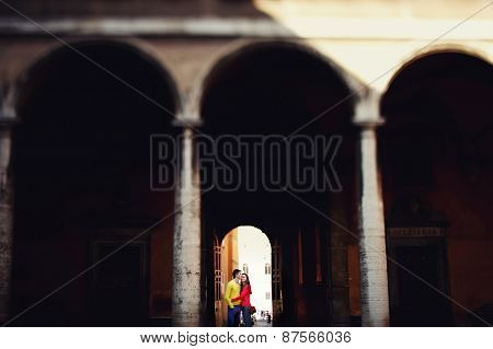Young Couple Standing In Arch Hospital In Rome