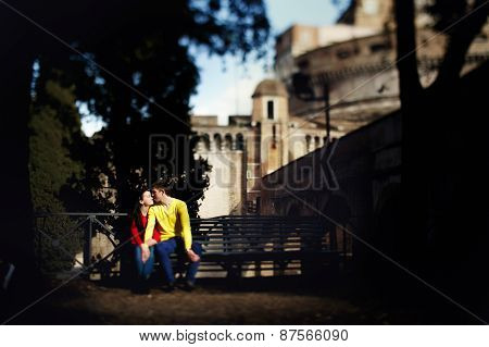 Young Couple Sitting On A Bench In The Background Castle Sant'angelo In Rome