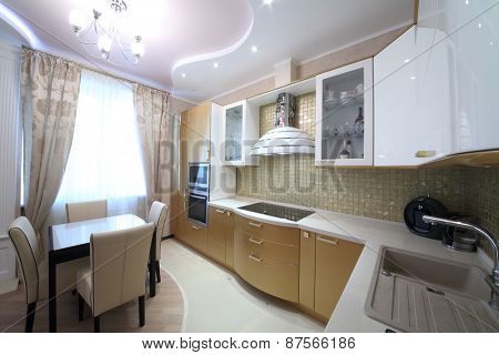 Modern kitchen interior with golden cabinets in the apartment