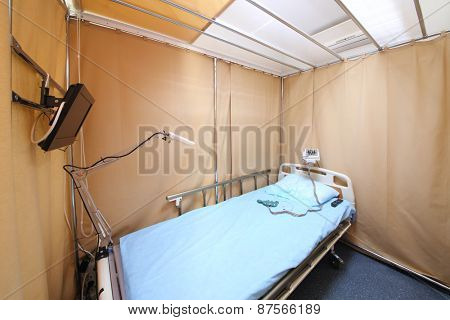 Simple interior hospital room with a bed, a TV and electroencephalograph
