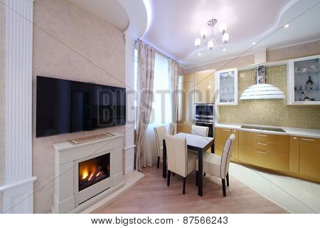 Interior of luxurious kitchen with golden cabinets and large fireplace in the apartment