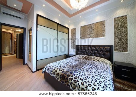 Luxurious bedroom in the Greek style with leopard print on the walls and bed