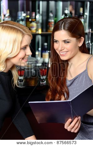 Two friends examine menu