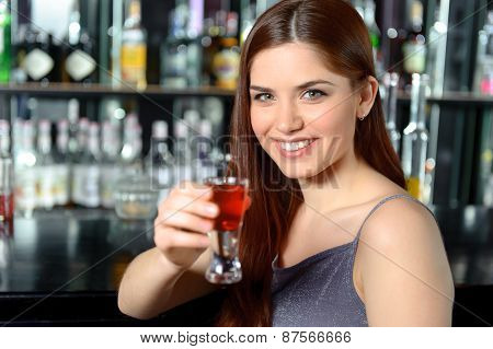 Young woman drinks cocktail