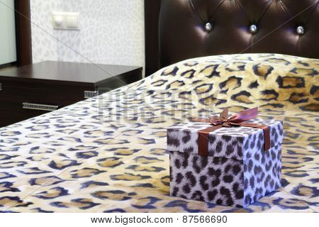Gift box with a leopard pattern on the bed with leopard bedspread