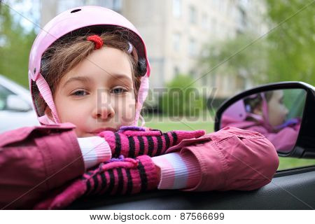 Girl in pink helmet leaning on the open window in the car