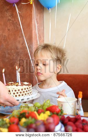 The little boy looks at the birthday cake with candles in cafe