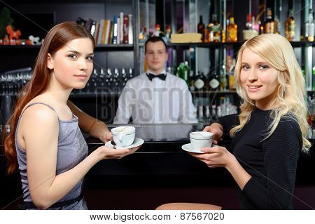 Friends drink coffee at a bar