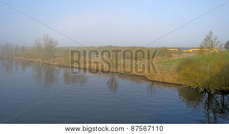 Train driving along a foggy canal in spring