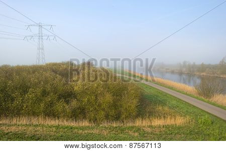 Road along a foggy canal in spring