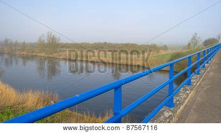 Blue bridge railing over a foggy canal in spring