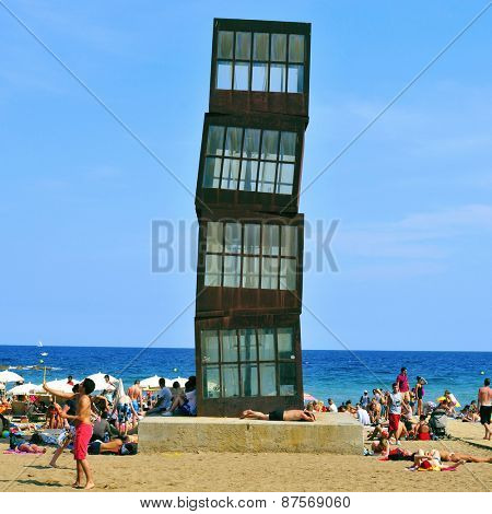 BARCELONA, SPAIN - AUGUST 19: Vacationers in the Barceloneta Beach on August 19, 2014 in Barcelona, Spain. A sculpture designed by artist Rebecca Horn in COR-TEN steel presides over this urban beach