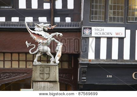 LONDON, UK - APRIL 07: Profile of City of London coat of arms dragon statue, with High Holborn street sign in the blurred background. April 07, 2015 in London.