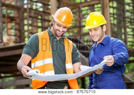 Smiling male architects analyzing blueprint outside at construction site
