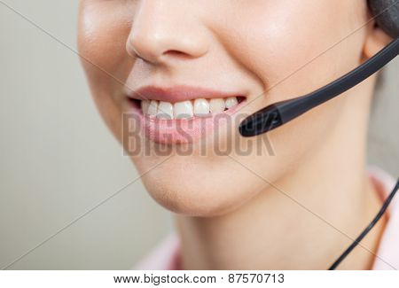 Closeup of smiling female customer service representative wearing headset in office