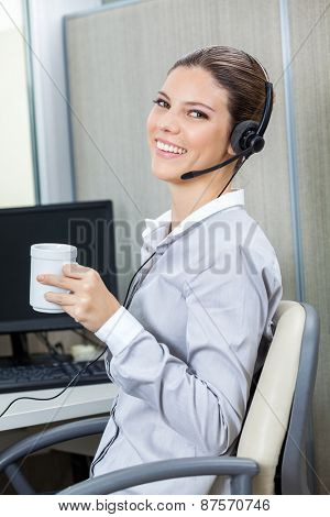 Portrait of young female customer service executive wearing headset while holding coffee cup in office
