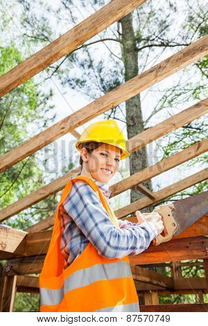 Portrait of smiling female worker cutting wood with handsaw at construction site