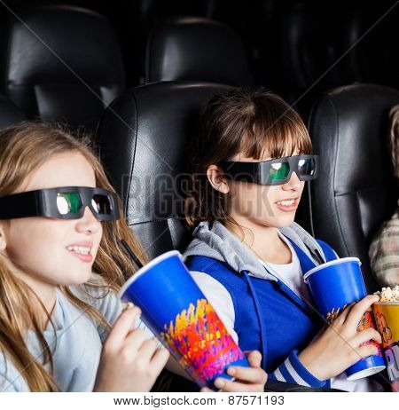 Children having snacks while watching 3D movie in cinema theater