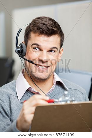 Happy customer service representative with clipboard looking away in office