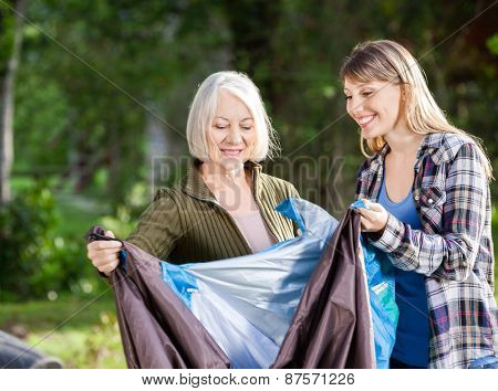 Smiling mother and daughter assembling tent in park at campsite