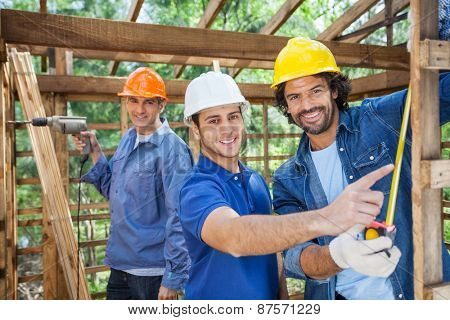 Portrait of happy male construction workers working in wooden cabin at site