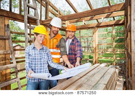 Male and female architects studying blueprint in wooden cabin at site
