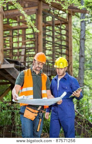 Male engineers with digital tablet analyzing blueprint outside wooden cabin at construction site
