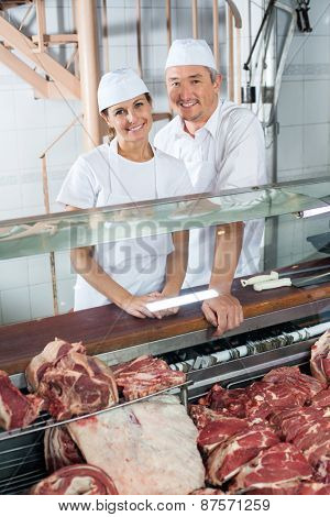 Portrait of confident butchers standing at meat counter in shop