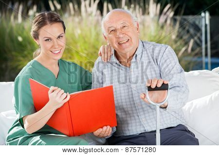Portrait of smiling female nurse and senior man with book at nursing home