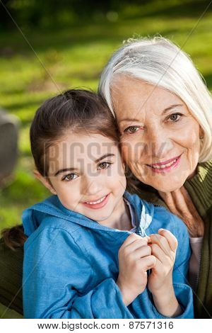 Portrait of happy girl with grandmother at campsite