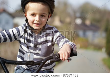 Boy riding a bicycle on a country road concept for healthy lifestyle, exercising and road safety