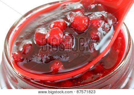 A spoon of Cranberry jam on top of a bottle, isolated on white background