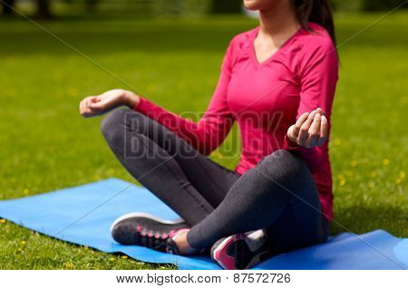sport, meditation, yoga, fitness and people concept - close up of woman meditating on mat at park