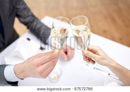 restaurant, people, celebration and holiday concept - close up of happy couple with glasses of champagne at restaurant
