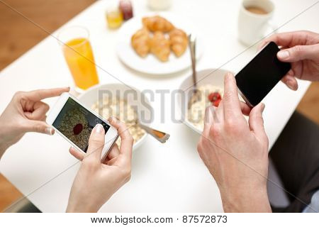 food, eating, people, technology and healthy food concept - close up of couple having breakfast and taking picture of food with smartphones at home