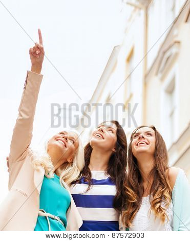 holidays and tourism concept - beautiful girls looking at something in the city