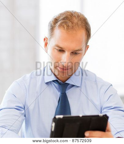handsome businessman with tablet pc in office