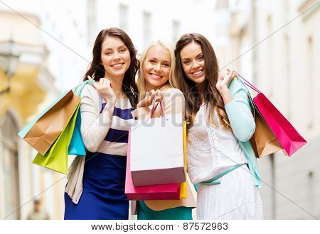 shopping and tourism concept - beautiful girls with shopping bags in city
