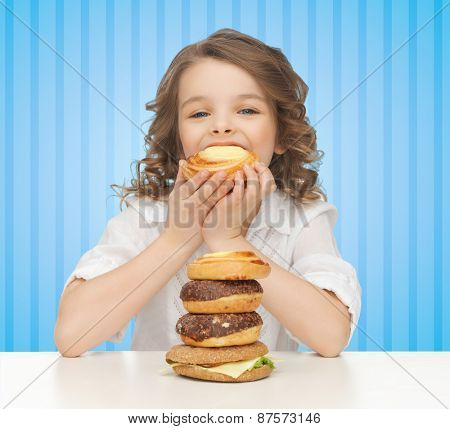 people, nutrition, childhood and health concept - happy little girl eating junk food over blue striped background
