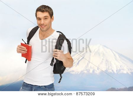 people, travel, tourism, japan and education concept - happy young man with backpack and book traveling over fuji mountain background