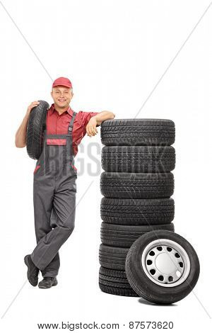 Full length portrait of a male worker carrying a tire in one hand and leaning on a stack of tires isolated on white background