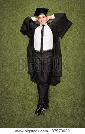 Vertical shot of a relaxed graduate student lying on a grass field and looking at the camera