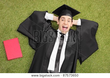 An excited student in graduation gown, lying on green grass with a book next to him and looking at the camera