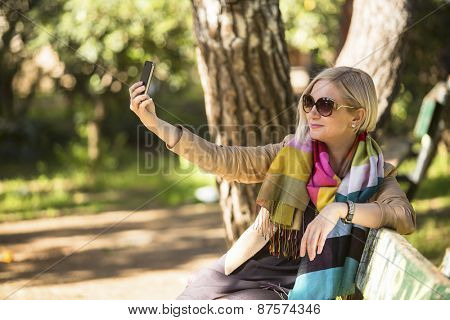 Young caucasian woman smiling for a self-portrait (selfie) on her smartphone, sitting on bench in the Park.