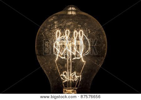 Vintage incandescent light bulb filament on black.
