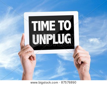 Tablet pc with text Time To Unplug with sky background