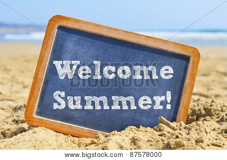 closeup of a chalkboard with a wooden frame and the text welcome summer written in it, placed on the sand of a beach